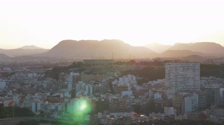 built up : Panning shot of Alicante, Spain. Cityscape with densely built-up residential areas. Scene with hills and mountains at sunset Stock Footage