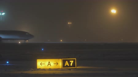 указатель : MOSCOW, RUSSIA - JANUARY 29, 2018: View to the runway and illuminated pointer at winter night, Aeroflot airplane gaining speed on take-off strip