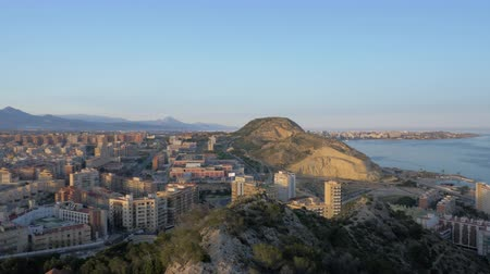 плотно : Panning shot of densely built-up Alicante city located on the coast of Mediterranean Sea, Spain. Scene at sunset with mountains in the distance