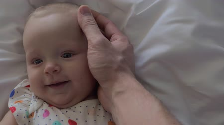 otcovství : Slow motion close-up shot of dad hand stroking gently baby head. Fathers love and care for little daughter Dostupné videozáznamy
