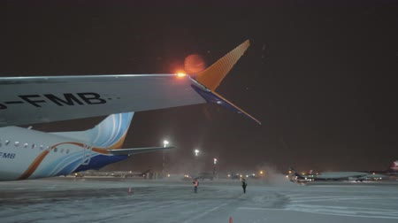 estacionado : MOSCOW, RUSSIA - JANUARY 29, 2018: Sheremetyevo Airport at winter night. View with Flydubai Boeing 737-8 MAX and vehicle cleaning snow