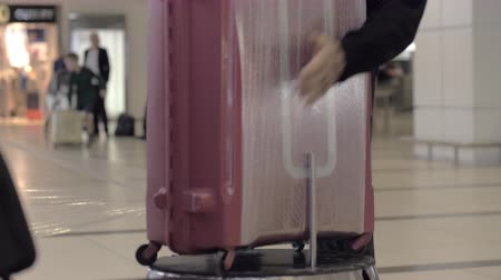 cling film : Man using luggage wrapping machine at the airport to protect the suitcase from damage and opening