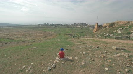 archeologie : Slow motion shot of the boy among the ruins of ancient city Hierapolis in Pamukkale, Turkey. He throwing the stone down the hill Dostupné videozáznamy