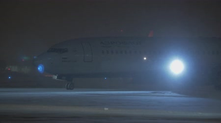snow plow : MOSCOW, RUSSIA - JANUARY 29, 2018: Aeroflot airplane Airbus A321 M. Musorgsky taxiing at Sheremetyevo Airport at night, snow plow driving by Stock Footage