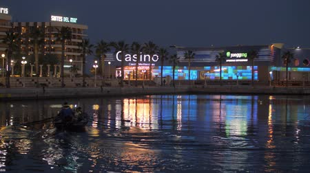 kaszinó : ALICANTE, SPAIN - APRIL 19, 2018: Rowing boat sailing in city harbour at night. Waterside view with hotel and gambling houses