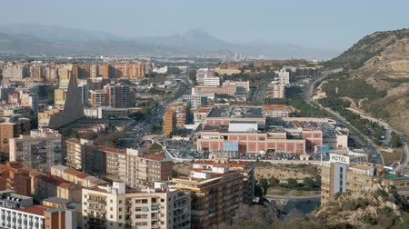 yoğunluk : ALICANTE, SPAIN - APRIL 19, 2018: City view with many buildings, houses and shopping mall Plaza Mar 2, car traffic on highway. Urban scene among picturesque hills Stok Video
