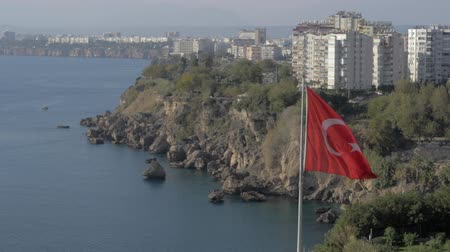 çok katlı : Slow motion shot of sea and rocky coast of Antalya with multistorey houses and hotels alongside, fluttering Turkish flag in foreground