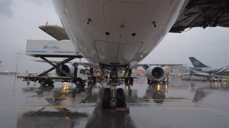 wheel loader : MOSCOW, RUSSIA - OCTOBER 04, 2017: Steadicam low angle shot of Korean Air airplane being prepared for the flight under the rain. View to the plane with container loader amd boarding bridge. Sheremetyevo Airport Stock Footage