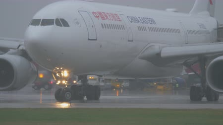 turn off : MOSCOW, RUSSIA - OCTOBER 04, 2017: China Eastern Airbus A330 leaving the terminal of Sheremetyevo Airport and taxiing to the runway on rainy evening. Major Chinese airline operating 214 destinations and having fleet size of 501 aircraft