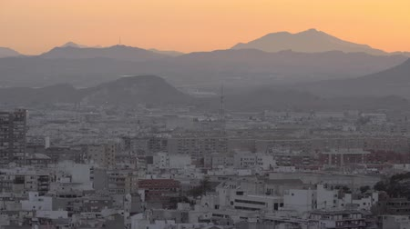 yoğunluk : Evening panorama of Alicante with densely built-up residential areas. Scene with hills and orange sky at sunset