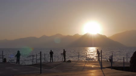 снасти : ANTALYA, TURKEY - NOVEMBER 11, 2017: Slow motion shot of some fishermen fishing from the pier. Scene with sunset over the mountains