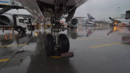 chock : MOSCOW, RUSSIA - OCTOBER 04, 2017: Underneath the airplane with wheel chock. View to Sheremetyevo Airport area with planes and air bridges