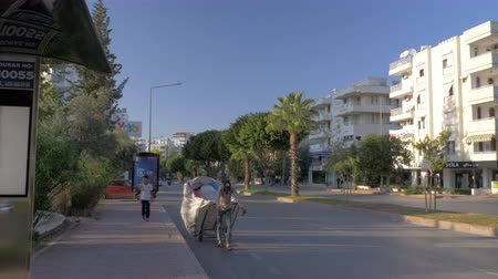nakládané : ANTALYA, TURKEY - NOVEMBER 11, 2017: City street with cars and bus driving on the road, man pulling loaded cart