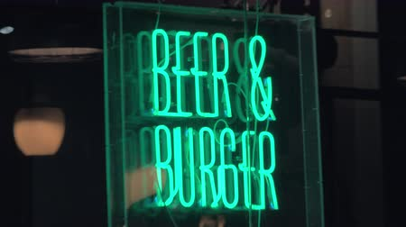 fast food : ALICANTE, SPAIN - APRIL 19, 2018: Illuminated neon banner Beer and Burger in the street at night. View with zooming in Stok Video
