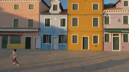 burano : BURANO, ITALY - APRIL 21, 2018: Colourful old houses and a little boy running in the street, view at sunset