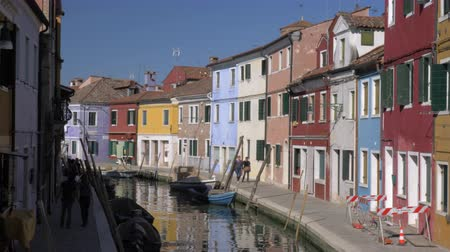 mooring : BURANO, ITALY - APRIL 21, 2018: Lovely colourful houses alongside the canal with moored boats and people walking. Scene of Burano island Stock Footage