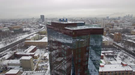 dull : Beautiful drone view of modern tower building standing on street of city on gray winter day