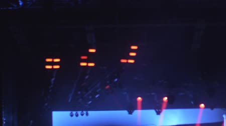truss : Medium shot of brightly colored lights flashing above the stage at a live concert