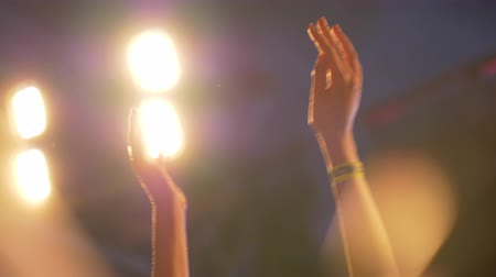 festivais : Close up slow motion shot of hands clapping with cheering fans at a live concert against bright lights Vídeos