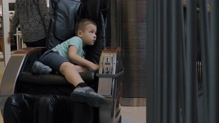 informal : A seven years old boy is lying in a massage chair in a mall. He is wearing a blue T-shirt and denim shorts. He is a bit bored as randomly moving his leg and looking around