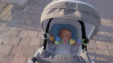 így : An adorable baby girl is sleeping in a moving baby carriage. It is sunny and warm outside so she is wearing just a light shirt. There are some colorful rattles attached to the carriage Stock mozgókép