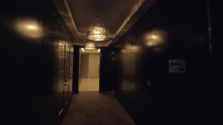 winda : A steadicam shot of a hotel hallway with presidential suits. The hallway is decorated with dark wooden panels, metal details and luxurious chandeliers. It is a bright empty hall at the end of it with two elevators