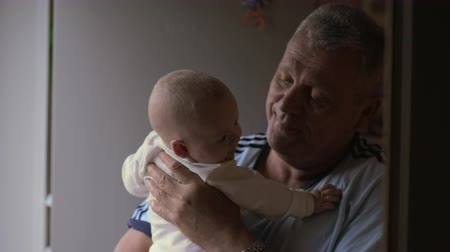 szopka : Medium shot of a grandfather holding and smiling at his newborn granddaughter