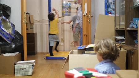 caregiver : Wide shot of home schooled children playing with various activities at a new home Stock Footage