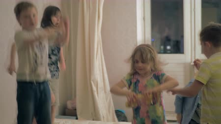 gritante : Medium shot of boys and girls excitedly jumping around the living room of a house