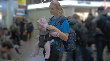nevinný : Medium shot of a cute baby in a baby carrier while waiting with her mother to travel in the airport terminal