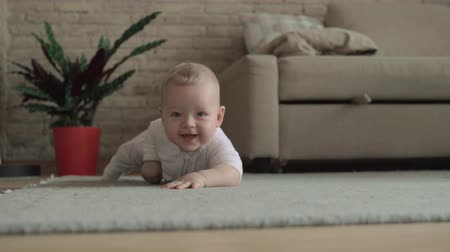 babygirl : Medium shot of an adorable baby girl playing on the carpet of her living room at home. Filmed from the floor Stock Footage
