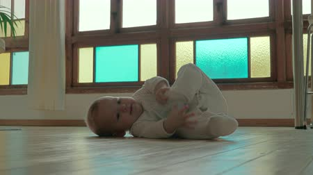 паркет : Adorable day playing with foot while rolling on floor in stylish room at home Стоковые видеозаписи