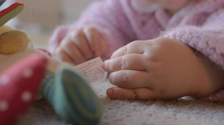 babygirl : Close up shot of a baby girl who plays on the carpet of her living room at home. Panning from hands to face. Stock Footage