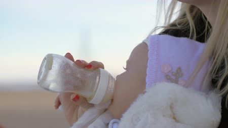 bottle feeding : Close up shot of a mother feeding her baby girl outside on a cold day at the seafront Stock Footage