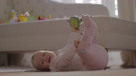 babygirl : Medium shot of an adorable baby girl in warm clothes playing on the floor