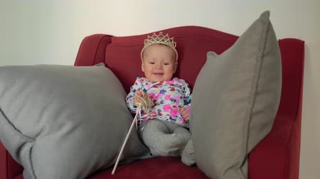 hůlky : Medium shot of a baby girl wearing a princess crown and holding a wand on a red chair