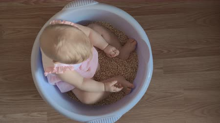 babygirl : Medium shot from above of a cute baby girl in a round blue tub full of lentils playing in her nursery at home