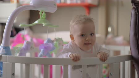 babygirl : Medium shot of a beautiful baby girl in a round white crib in her nursery at home Stock Footage