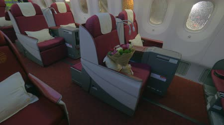 first class : Wide shot of a jet airplane interior view without people seated inside the cabin, first class, greeting flowers