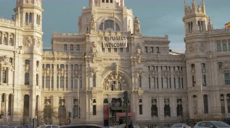 лозунг : MADRID, SPAIN - JANUARY 17, 2018: Madrid City Hall building with a poster Refugees Welcome on Plaza Cibeles with car traffic Стоковые видеозаписи