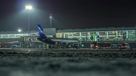 eend : MOSCOW, RUSSIA - NOVEMBER 29, 2017: Timelapse shot of Sheremetyevo Airport at winter night. Vehicles traffic and loading cargo containers into Aeroflot aircraft Stockvideo