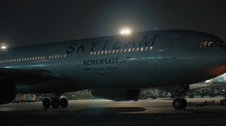 tow : MOSCOW, RUSSIA - NOVEMBER 11, 2017: Air tow tractor pulling Aeroflot airplane in SkyTeam livery at Sheremetyevo Airport at winter night. Airline alliance with 20 carriers from five continents