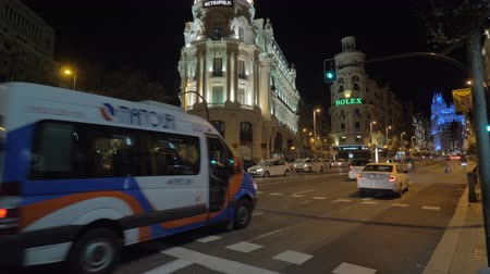 köşeler : MADRID, SPAIN - JANUARY 17, 2018: Night view of Gran Via street with car traffic, Metropolis Building and The Grassy Clock and Watch Museum with Rolex banner Stok Video