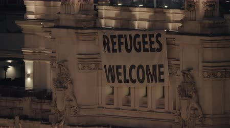 лозунг : MADRID, SPAIN - JANUARY 17, 2018: Night view of Refugees Welcome banner hanging on the building of Madrid City Hall