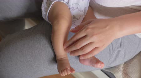 amado : Slow motion shot of loving mother holding baby daughter in arms and touching gently little feet and toes. Mum and child bonding Stock Footage
