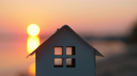 mülkiyet : Close-up shot of house model on the beach on background of sea and sunset. Real estate, home and mortgage symbol Stok Video