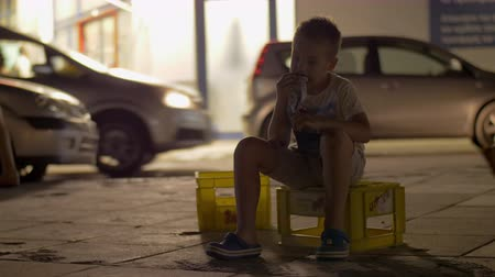 бездомный : Abandoned child eating in the street. He sitting on the plastic box, indifferent people passing by