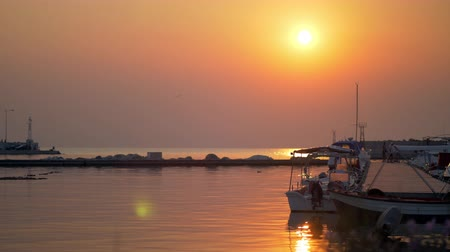 mooring : Cinemagraph - Sunset waterscape with harbour and tied up boats. Golden sunlight reflecting in water. Quiet marine scene