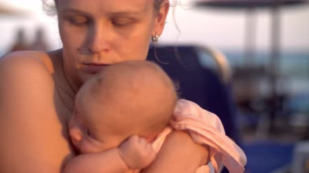 wistful : Slow motion shot of a mother with thoughtful look holding in hands baby daughter and kissing her. Shot at the beach at sunset