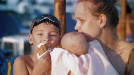 waffle : Slow motion shot of a boy eating waffle cone ice cream when relaxing at the beach with mum and baby sister